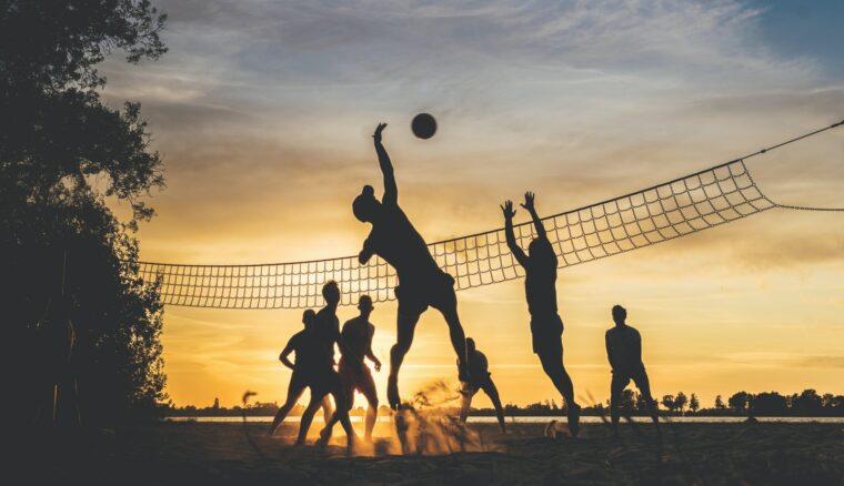 silhouette of people playing basketball during sunset